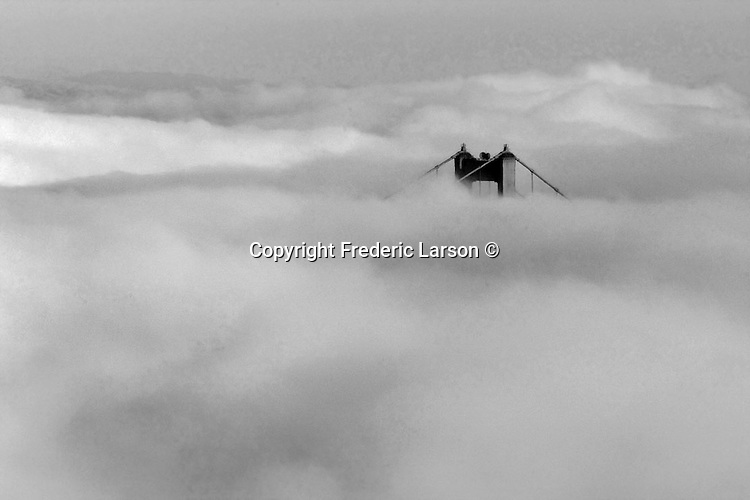 Black and white image of San Francisco fog over the south tower of the Golden Gate Bridge.