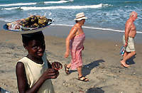 Gambia. Kombo beach. Atlantic ocean. Kombo beach is 25 km away from the capital Banjul.  An old couple of white tourists walk on the beach while a young black girl carries a tray on her head and sells bananas and peanuts . © 2000 Didier Ruef