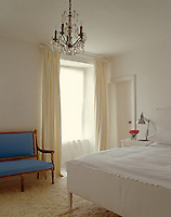 A stark white bedroom with a blue Swedish-style sofa on a shag-pile carpet