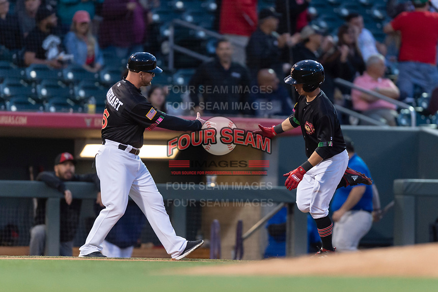 El Paso Chihuahuas shortstop Luis Urias (3) is congratulated by hitting coach Morgan Burkhart (58) after hitting a home run during a Pacific Coast League game against the Albuquerque Isotopes at Southwest University Park on May 10, 2019 in El Paso, Texas. Albuquerque defeated El Paso 2-1. (Zachary Lucy/Four Seam Images)