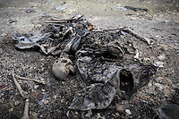 In this Monday, Dec. 10, 2012 photo, rests of a human body lies on a street after being discovered allegedly burned and abandoned at the frontline in Aleppo, Syria. (AP Photo/Narciso Contreras)