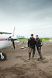 USA, Alaska, Homer, a couple stand in front of a small plane on the beach at Hallow Bay, Katmai National Park, Katmai Peninsula, Gulf of Alaska