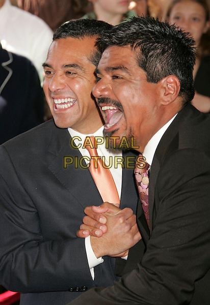 L.A. MAYOR ANTONIA VILLARAIGOSA & GEORGE LOPEZ.George Lopez Star on The Hollywood Walk Of Fame, Hollywood, California, USA..March 29th, 2006.Photo: Russ Elliot/AdMedia/Capital Pictures.Ref: RE/ADM.headshot portrait facial hair laughing mouth open shaking hands.www.capitalpictures.com.sales@capitalpictures.com.© Capital Pictures.