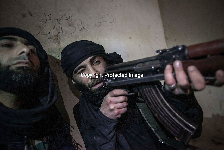 In this Wednesday, Dec. 05, 2012 photo, Syrian rebel fighters aim their weapons to the entrance of a house building as they wait for their enemy to appears during heavy clashes in Aleppo, Syria. (AP Photo/Narciso Contreras)