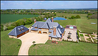 BNPS.co.uk (01202 558833)<br /> Pic:  KnightFrank/BNPS<br /> <br /> Back to the future...<br /> <br /> A stunning new Arts and Crafts style country manor which comes with its own lake, swimming pool, tennis court and summer house has come on to the market for £4.95million.<br /> <br /> Recently built Thakeham Manor, which also has a helipad, is set in 16 acres of landscaped parkland near Pulborough, West Sussex.<br /> <br /> Its eye-catching design, inspired by the famous early 20th century architect Edwin Lutyens, includes a slate roof, stone quoins and brick buttresses, while inside it is full of glamorous modern touches.<br /> <br /> The luxurious property has five bedrooms, five bathrooms and six reception rooms, and its grounds contain a heated swimming pool and decking area, a circular cushioned seating area and a tennis court.