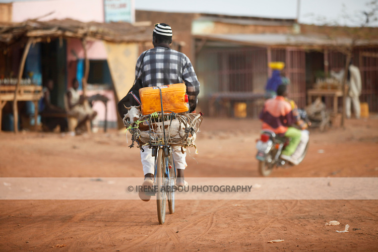 "In West Africa, certain villages have markets that ""assemble"" at regular intervals, such as weekly or every three days.  The sheep on the back of this man's bicycle is destined for sale at Djibo's weekly Wednesday market in northern Burkina Faso, where people from villages around the region converge to buy and sell food, livestock, and other goods and services."
