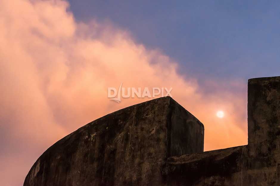 A nearly full moon rises over the ramparts of Fort Belgica.