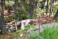 Waterfall river deck and garden, gorgeous secluded private landscaping with decking over rushing water, stone pathway, plants, containers, tall trees and woodlands