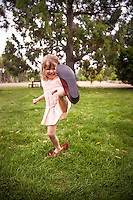 Girl playing with her mothers red shoes on lawn, New Zealand - stock photo, canvas, fine art print