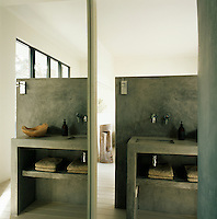A concrete partition unit encompassing a hand basin and shelving separates a bathroom area from a bedroom. A full height mirror creates a sense of space.