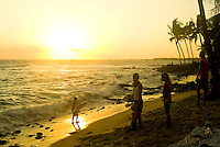 Children look for a last wave to play in as the sun sets at Hano beach in Kona on the Big Island of Hawaii.