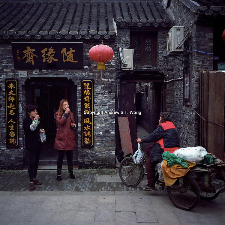Chinese vendors eat snacks and chat at Dongguan Old Street in Yangzhou, Jiangsu province, 2012. (Mamiya 6, 75mm, Kodak Ektar 100 film)