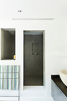 The minimalist bathroom features white walls and flooring and a walk-in, recessed shower room. A green striped towel hanging over a rail brings a touch of colour to the room.