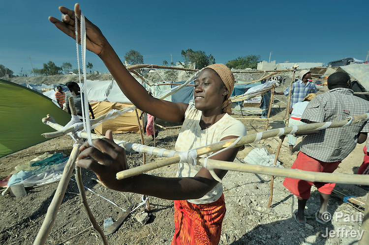 A woman fastens sticks together with strips of cloth as she builds a temporary home in a spontaneous camp for quake survivors being established in Croix-des-Bouguets, Haiti, north of the capital Port-au-Prince. Quake survivors continue to move as aftershocks continue, and reports of aid deliveries in one camp will provoke families from other camps to migrate there.