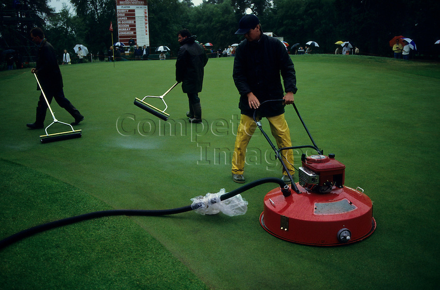 Ground keepers removing water from the greens with rollers and vacuum