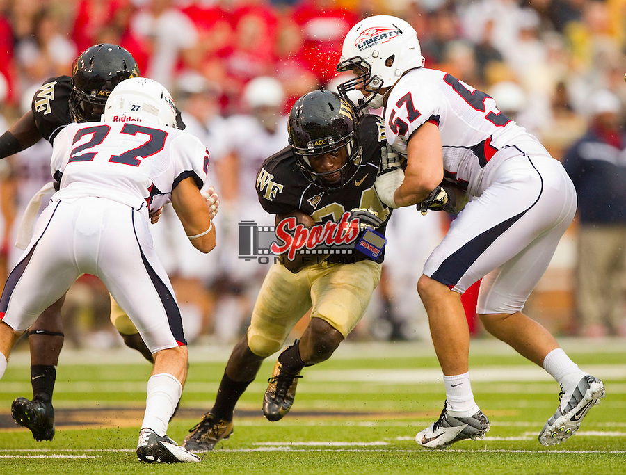 Duran Lowe #34 of the Wake Forest Demon Deacons pushes past Nick Martin #57 of the Liberty Flames as he tries to get to the punter at BB&T Field on September 1, 2012 in Winston Salem, North Carolina.  The Demon Deacons defeated the Flames 20-17.  (Brian Westerholt/Sports On Film)