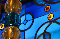 Detail of the stained glass window, with blue glass and leadwork in circles and the interlacing patterns reminiscent of the Neo-Romanesque style of the 19th century, made by Ateliers Loire, Chartres, and blue and gold glass beads made by Murano glassmaker Salviati, in the Bell tower room themed 'Le Merveilleux' or The Supernatural, first floor, in Le Tresor de la Cathedral d'Angouleme, in Angouleme Cathedral, or the Cathedrale Saint-Pierre d'Angouleme, Angouleme, Charente, France. The 12th century Romanesque cathedral was largely reworked by Paul Abadie in 1852-75. In 2008, Jean-Michel Othoniel was commissioned by DRAC Aquitaine - Limousin - Poitou-Charentes to display the Treasure of the Cathedral in some of its rooms, which opened to the public on 30th September 2016. Picture by Manuel Cohen. L'autorisation de reproduire cette oeuvre doit etre demandee aupres de l'ADAGP/Permission to reproduce this work of art must be obtained from DACS.