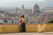 A young man and woman kiss on a terrace overlooking the Duomo, Florence, Italy.