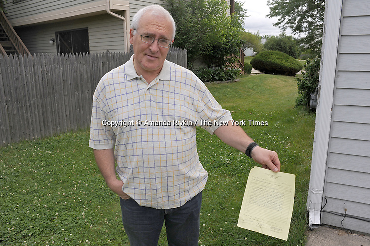 Mikhail Mazo, 52, a Russian immigrant, holds the warning notice he received for not trimming his lawn from the suburban Chicago municipality of Buffalo Grove, Illinois on July 2, 2009.