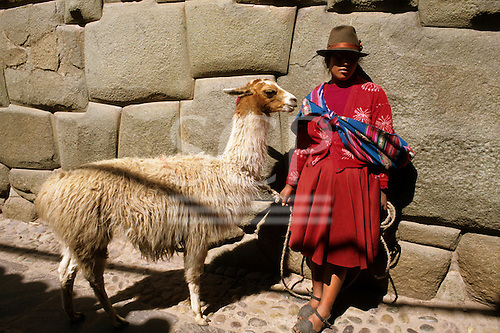 Cusco, Peru. Woman in traditional dress with a llama in Hatunrumiyoc by the famous twelve-sided stone.