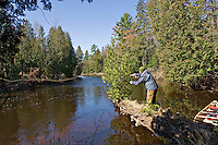 A fly fisherman fishes while canoeing the Escanaba River in the Upper Peninsula of Michigan.