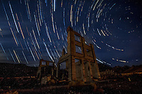 Star trails at the ghost town of Rhyolite Nevada.  John S Cook and Company Bank Building remains in the Ghost Town of Rhyolite Nevada. The 3 story building was the tallest building in town and was completed in 1907.<br /> <br /> Rhyolite is a ghost town in Nye County, in the U.S. state of Nevada. It is located in the Bullfrog Hills, about 120 miles (190 km) northwest of Las Vegas, near the eastern edge of Death Valley.