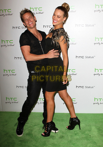 Damian Whitewood & Peta Murgatroyd.The HTC Statusª Social Launch Event held at Paramount Studios in Hollywood, California, USA..July 19th, 2011.full length dress sleeves hands on hips black brown feather hair up bun cut out away cleavage open toe sandals shoes  smiling bending leaning jeans denim side arm around waist funny .CAP/ADM/KB.©Kevan Brooks/AdMedia/Capital Pictures.