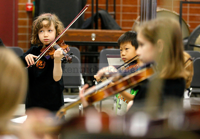 Anna Davis, 8, participates in violin and viola exercises at the beginning of the UK String Project class in the Fine Arts Building Saturday morning. The UK String Project is affiliated with the National Strings Project Consortium that is dedicated to increasing the number of children who play stringed instruments..Photo by Zach Brake | Staff