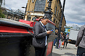 A young woman uses a mobile phone in Camden Town, London.