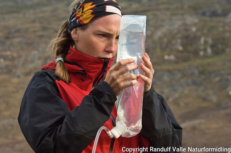 Jente studerer vann i vannpose ---- Girl checking water in transparent water bag