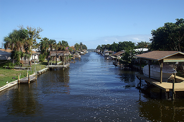 This residential canal was created prior to 1967 by a construction method called pump and fill.  This area was originally coastal marsh.  Dredges were brought in to dredge out the canal, the dredged material was pumped into the area adjacent to the canal to created a strip of land wide enough to build a street with houses on each side of the street.  A moritorium on this construction practice was imposed in 1967 when the importance of the coastal marshes to fishery populations was understood.  This kind of construction today would require permits from mulitple agences, which would be denied.