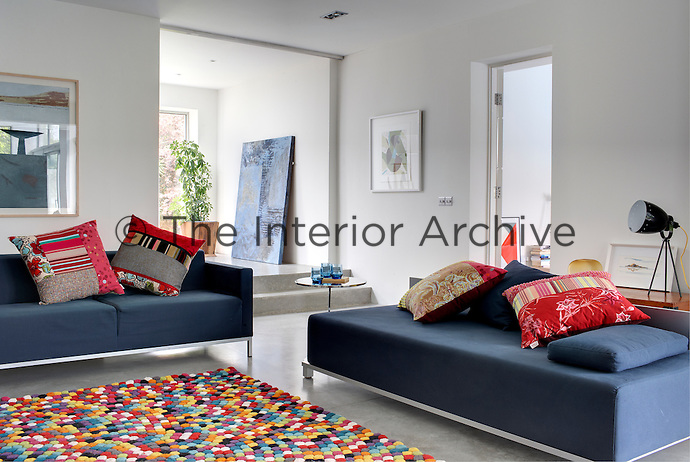 In the living room a pair of matching sofas has been arranged around a vibrant multi-coloured contemporary rug with a collection of colourful scatter cushions; the framed prints are works by Stephen Vaughan