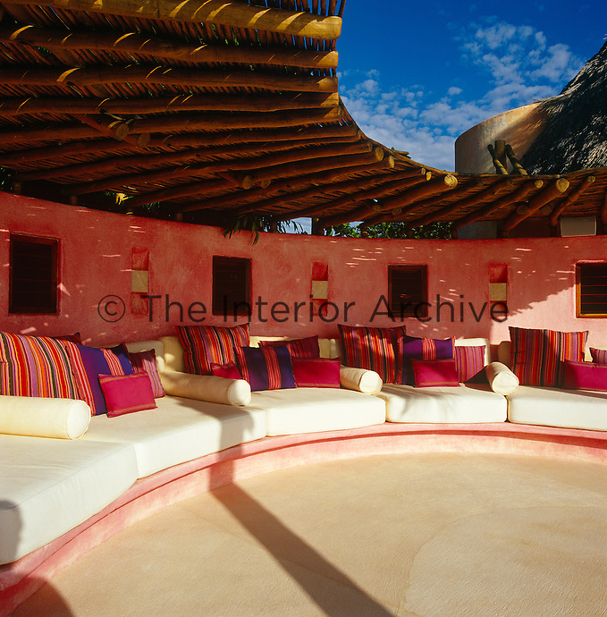 Brightly coloured cushions are scattered on an upholstered banquette in the shade of a palapa on the open terrace of the property