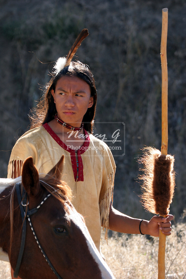 A Native American Indian boy wearing a feather standing next to a horse holding a coup stick with buffalo hide on it