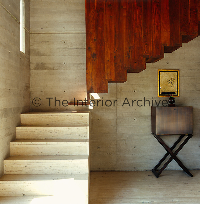 The cantilevered staircase is made of two different materials, the lower of concrete and the upper of wood
