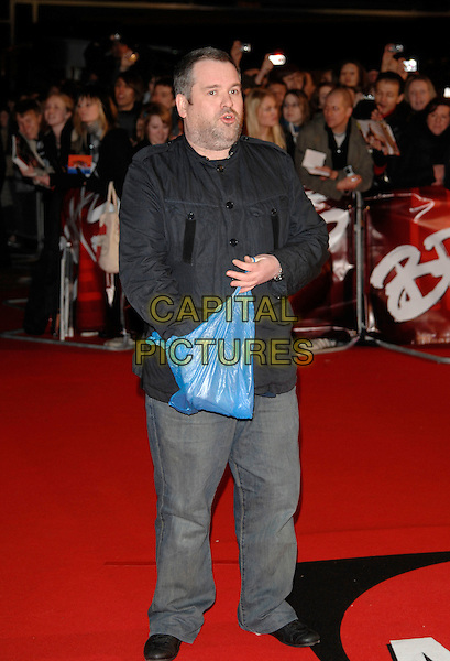 CHRIS MOYLES.The Brit Awards arrivals at Earl's Court, London England. .14th February 2007.brits full length jeans denim black jacket blue plastic bag carrier.CAP/PL.©Phil Loftus/Capital Pictures