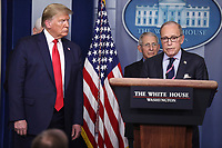 Director of the National Economic Council Larry Kudlow, right, speaks as United States President Donald J Trump, left, listens during a press conference with members of the coronavirus task force in the Brady Press Briefing Room of the White House on March 24, 2020 in Washington, DC.  <br /> At center is Director of the National Institute of Allergy and Infectious Diseases at the National Institutes of Health Dr. Anthony Fauci.<br /> Credit: Oliver Contreras / Pool via CNP/AdMedia