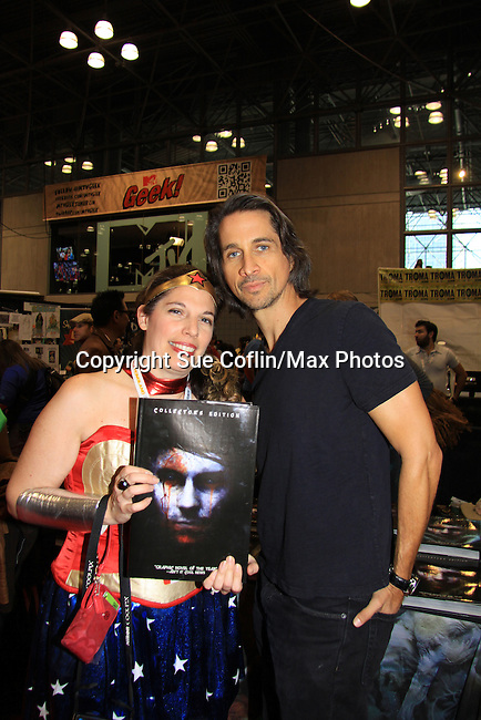 "General Hospital Michael Easton (One Life To Live, Port Charles, Days of Our Lives) poses with fan Carolan at the New York Comic Con 2012 to show fans and others ""Soul Stealer Collector's Edition"" which he cowrote and  was in a booth with Christopher Shy on October 13, 2012 at the Javits Center, New York City, New York. (Photo by Sue Coflin/Max Photos)"