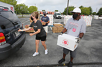 Food is loaded into vehicles Tuesday, July 28, 2020, at Arvest Ballpark in Springdale. The Salvation Army of Northwest Arkansas in partnership with the Church of Jesus Christ of Latter-Day Saints distributed 800 boxes of food to provide relief during the covid-19 pandemic. Both organizations have worked together nationally and saw this as an opportunity to work together locally. Donations were also contributed by The Pack Shack and Tyson Meals that Matter. The use of Arvest Ballpark was made possible by the Northwest Arkansas Naturals. For more information about the group visit nwaadoptacop.com. Check out nwaonline.com/200729Daily/ and nwadg.com/photos for a photo gallery.<br /> (NWA Democrat-Gazette/David Gottschalk)<br /> <br /> SZ FEA FOOD 7-29