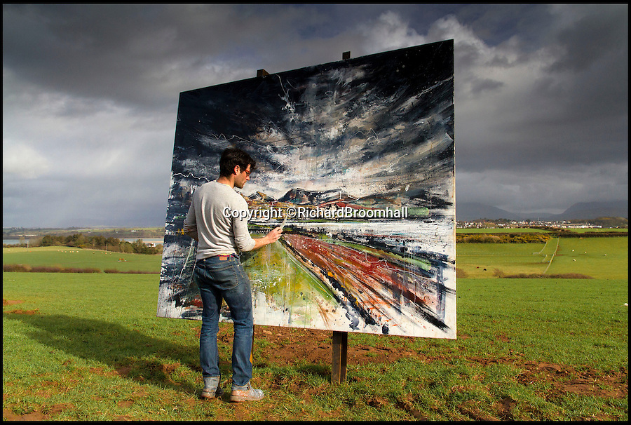 BNPS.co.uk (01202 558833)<br /> Pic: RichardBroomhall/BNPS<br /> <br /> Artist in Residence...Garratt in his element, at work on his Menai Straits canvas.<br /> <br /> Artist Anthony Garratt is giving a whole new meaning to landscape painting - his incredible pieces aren't just of the landscape, they're in it too.<br /> <br /> The 35-year-old painter from Bristol has created four canvasses on the island of Anglesey as part of a new outdoor art installation and the paintings will remain in the exact spot they were painted until October.<br /> <br /> Mr Garratt spent several days on each of the giant 8ft-wide scenes, which are exposed to the elements and can be enjoyed by walkers as well as art fans. <br /> <br /> The landscapes had to be created on marine board - a thick marine plywood treated with sealant and epoxy, like a boat - rather than normal canvas, coated with five layers of varnish afterwards and mounted on bespoke steel frames to ensure they survive any harsh outdoor conditions.