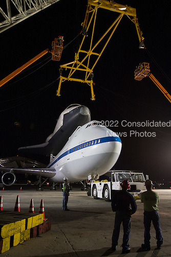 A yellow sling is lowered onto space shuttle Enterprise, which sits atop NASA's 747 Shuttle Carrier Aircraft (SCA) prior to it being demated a few hours later at John F. Kennedy (JFK) International Airport in New York, Saturday, May 12, 2012. The shuttle will be placed on a barge that will move by tugboat up the Hudson River to Intrepid in June. The shuttle will be lifted by crane and placed on the flight deck of the Intrepid, where it will be on exhibit to the public starting this summer in a temporary climate-controlled pavilion..Mandatory Credit: Kim Shiflet / NASA via CNP