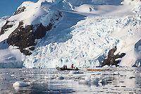 A zodiac tows a sea kayak back to the ship after a paddle excursion in Cierva Cove on the Antarctic Peninsula.