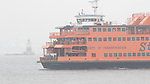 Staten Island Ferry, The Spirit of America about to pass the Robbins Reef Lighthouse in New York Harbor on a foggy day.