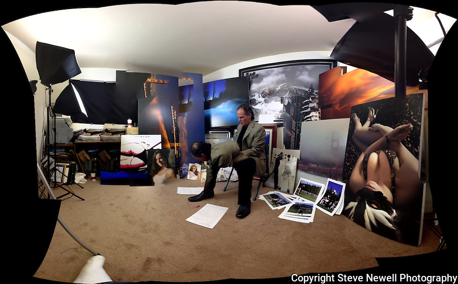 """The Studio""  An action shot of me shooting a video talking about my work while surrounded by various samples in my studio.  I specialize in large oversized landscapes but have shot several types of professional photography over the years.  I do all of my own printing using a 44"" wide Epson Stylus Pro 9900 using their latest UltraChrome K3 HDR archival inks(11 different colors). I only use the best quality materials to produce my work.  As you can see in the photo I have some of my photographs custom framed(by an excellent local custom framer) and also print on canvas.  I offer GALLERY QUALITY WITHOUT THE GALLERY PRICES !  I also print for other artist and provide photo/video services for those in need."