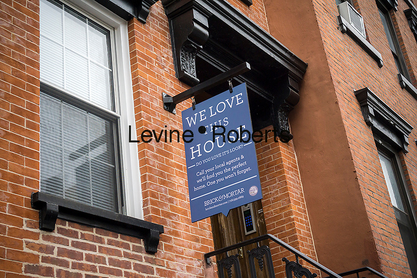 A sign hanging from a building in Williamsburg, Brooklyn in New York on Sunday, May 1, 2016 advertises the services of a real estate broker. (© Richard B. Levine)