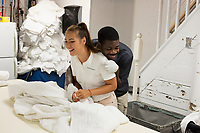 Allan Baxter, 40, (right) and Stela Poparova, 24, work in the laundry of the Harborside Inn in Edgartown, Martha's Vineyard, Massachusetts, USA, on Tues., July 25, 2017.  From St. Mary Parish, Jamaica, Baxter has worked at the hotel on an H2B visa for seasonal foreign workers. He spent last winter working in Stowe, Vermont, as well. The hotel has had difficulty this year getting as many H2B visas as it had in previous years. As a result, Baxter is the only person working in the laundry room on most days; it was a two-person job last year. Workers from other areas of the hotel, like Poparova, who is officially employed as a pool attendant, sometimes work short shifts in the laundry room to help Baxter. Poparova is from Plovdiv, Bulgaria, and has a J1 visa for students. She is a linguisitics student at New Bulgarian University in Sofia, Bulgaria.