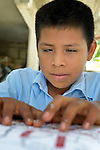 Eleven-year old Juan Lopez reads a map with Braille lettering during class in a school in Zipolite, a town in Oaxaca, Mexico. Juan is blind, and yet refuses to be sidelined. He rides his bike, for example, with his sister's help. She perches on the back and signals him which way to steer by pinching his shoulder. If she pinches his right shoulder, for example, he goes right. The harder the pinch, the sharper the turn.