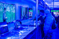 Visitors at the Intel Experience Store pop-up shop (under blue lighting) in the Nolita neighborhood in New York on Saturday, November 23, 2013. The promotional event, which is part of a world tour, aims to expose consumers to various brands of computers, mostly touch screen pc's running Windows  8, all running on Intel chips. Because of tablets, smartphones and other mobile gadgets there has been a drop in sales in laptops and other personal computers. (© Richard B. Levine)