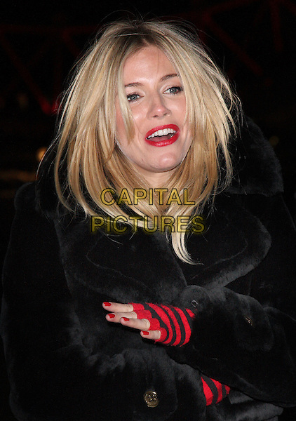 SIENNA MILLER.Sienna Miller lights the 'London Eye' red for World Aids Day 2010, London, England..December 1st 2010.half length black jacket fur arms crossed red striped stripes gloves lipstick make-up arms crossed mouth open funny nail varnish polish .CAP/ROS.©Steve Ross/Capital Pictures.