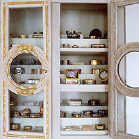 In the living room glassed-in gilt picture frames are used as doors for a built-in cabinet with shelves displaying a collection of ornate gilded antique boxes